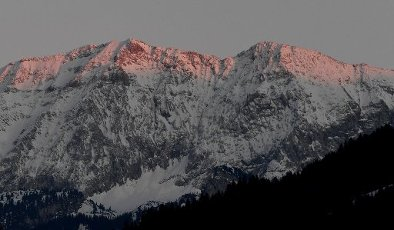 05 April 2020, Bavaria, Garmisch-Partenkirchen: The snow-covered peaks of the Wettersteinwand are illuminated red by the sun in the evening. Photo: Angelika Warmuth/