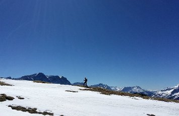 05 April 2020, Bavaria, Griesen: A hiker walks over last snow fields near the summit of Friederspitze in the Ammergau Alps, in the background you can see the Zugspitze on the left. Photo: Angelika Warmuth/