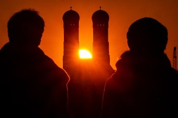 05 April 2020, Bavaria, Munich: A couple watches the sun set behind the Frauenkirche with its two 99-metre-high towers in the heart of the Bavarian capital. Photo: Peter Kneffel/