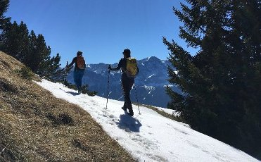 dpatop - 05 April 2020, Bavaria, Griesen: Hikers walk over the last snowfields to the Friederspitze in the Ammergau Alps, in the middle you can see the summit of the Zugspitze. Photo: Angelika Warmuth/
