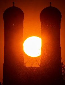 05 April 2020, Bavaria, Munich: The sun sets between the two 99-metre high towers of the Frauenkirche, which stands in the heart of the Bavarian capital. Photo: Peter Kneffel/