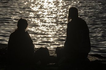 10 April 2020, Berlin: A woman and a man sit in the evening on the banks of the Spree in Treptower Park. Photo: Paul Zinken/