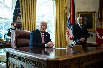 United States President Donald J. Trump and US Vice President Mike Pence listen during an Easter blessing in the Oval Office of the White House on Friday, April 10, 2020 in Washington. Credit: Al Drago / Pool via CNP | usage
