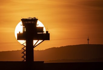 10 April 2020, Hessen, Frankfurt/Main: The sun sets behind the tower of the German Air Traffic Control (DFS) at Frankfurt Airport without any aircraft in the sky. Regular flight operations have come to an almost complete standstill due to the worldwide corona pandemic. Photo: Boris Roessler/