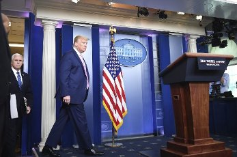 United States President Donald J. Trump arrives to deliver remarks at a Coronavirus briefing at the White House on Friday, April 10, 2020 in Washington, DC. With the U.S. death toll from the coronavirus pandemic expected to peak over the weekend, most of the country will be firmly under stay-at-home orders on Easter Sunday. At left is US Vice President Mike Pence. Credit: Kevin Dietsch / Pool via CNP | usage