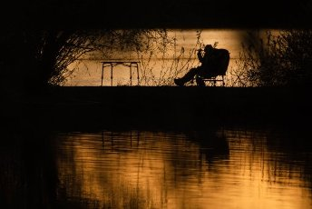 10 April 2020, Bavaria, Breitengüßbach: A woman sits on a fishing chair at dusk on the lakeside and drinks a wine. Photo: Nicolas Armer/