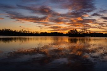 10 April 2020, Bavaria, Breitengüßbach: The colourful evening sky is reflected in the water of the quarry pond of Breitengüßbach. Photo: Nicolas Armer/