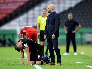 04 July 2020, Berlin: Football: DFB Cup, Final: Bayer Leverkusen - FC Bayern Munich, in the Olympic Stadium. Leverkusen\'s Lars Bender (l) kneels next to coach Peter Bosz during the match. Photo: Annegret Hilse\/Reuters\/pool\/dpa - IMPORTANT NOTE: In accordance with the regulations of the DFL Deutsche Fußball Liga and the DFB Deutscher Fußball-Bund, it is prohibited to exploit or have exploited in the stadium and\/or from the game taken photographs in the form of sequence images and\/or video-like photo series