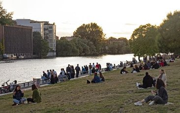 11 July 2020, Berlin: People sit on the meadows at the East-Side-Gallery and enjoy the sunset at the Spree. Photo: Paul Zinken