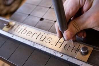 13 July 2020, Berlin: Before a visit by the Federal Minister of Labour Hubertus Heil, a construction mechanic shows how he makes a name plate for the minister. Heil informs himself in the metal workshop of the Union of Social Institutions (USE) for people with disabilities about the situation of employees in the Corona crisis. Photo: Lennart Stock