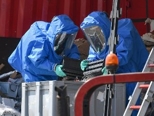 13 July 2020, Hessen, Butzbach: After an accident on the A5 Kassel - Frankfurt near Butzbach, firefighters in special suits unload a truck that was charging batteries. In the rear-end collision involving several trucks, batteries had been damaged and battery acid leaked. The A5 is closed for hours because of the clean-up work. Photo: Arne Dedert