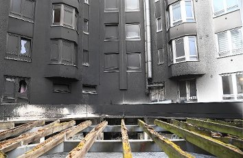 13 July 2020, Berlin: Sooty apartments in the Neukölln district. During the night six cars had burned in an open garage. Due to the heavy smoke, a neighboring apartment building was also affected. Photo: Britta Pedersen\/dpa-Zentralbild