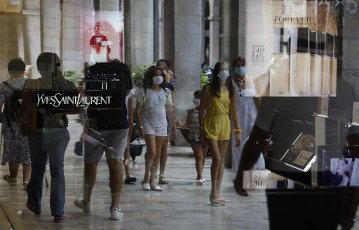 13 July 2020, Spain, Palma: People wearing mouthguards are reflected in the window of a shop in the centre of Palma. On Mallorca and the other Balearic Islands, an extensive compulsory wearing of masks is to come into force on Monday due to the Corona pandemic. Photo: Clara Margais