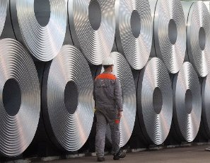 12 July 2020, Lower Saxony, Salzgitter: An employee walks past coiled steel (coils) at Salzgitter AG. The steel manufacturer Salzgitter AG wants to significantly reduce CO2 emissions. As part of the company\'s climate strategy, coal is to be gradually replaced by hydrogen and electricity from renewable sources in the production of iron. The end result would be a 95 percent reduction in CO2 emissions. Photo: Julian Stratenschulte