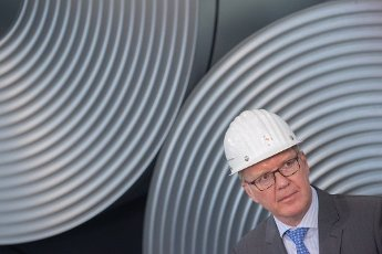 12 July 2020, Lower Saxony, Salzgitter: Heinz Jörg Fuhrmann, Chairman of the Executive Board of Salzgitter AG, is standing in front of coiled steel (coils) at the Salzgitter AG plant. The steel manufacturer Salzgitter AG wants to significantly reduce CO2 emissions. As part of the company\'s climate strategy, coal is to be gradually replaced by hydrogen and electricity from renewable sources in the production of iron. The end result would be a 95 percent reduction in CO2 emissions. Photo: Julian Stratenschulte