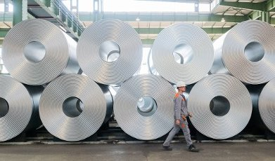 13 July 2020, Lower Saxony, Salzgitter: An employee walks past coiled steel (coils) at Salzgitter AG. The steel manufacturer Salzgitter AG wants to significantly reduce CO2 emissions. As part of the company\'s climate strategy, coal is to be gradually replaced by hydrogen and electricity from renewable sources in the production of iron. The end result would be a 95 percent reduction in CO2 emissions. Photo: Hilal Özcan