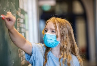 12 August 2020, North Rhine-Westphalia, Münster: A pupil of class 8a of the comprehensive school in Münster, stands after the summer holidays with a mouth and nose mask in front of a blackboard and solves an arithmetic problem. After the summer holidays, North Rhine-Westphalia is back in regular school operation. Photo: Guido Kirchner\/dpa