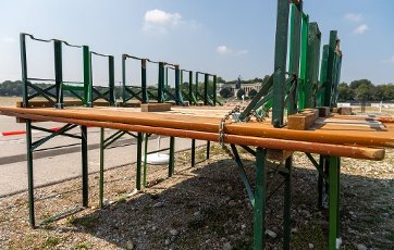 12 August 2020, Bavaria, Munich: Chained beer benches stand on the otherwise almost empty Oktoberfest grounds. Normally the construction of the biggest folk festival in the world would be in full swing at this time. In the background you can see the Bavaria. Photo: Peter Kneffel\/dpa