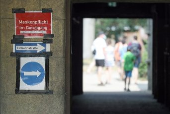 12 August 2020, Lower Saxony, Osnabrück: A sign in the zoo indicates that visitors are still required to wear masks and that special routing is required due to the Corona pandemic. Photo: Friso Gentsch\/dpa