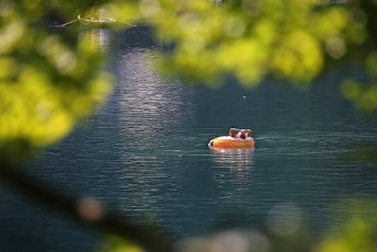12 August 2020, Bavaria, Schwangau: A man is floating in a floating tyre on the cool water of the Alpsee. Photo: Karl-Josef Hildenbrand\/dpa