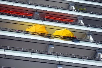 12 August 2020, Berlin: With parasols, residents of a high-rise building in the Mitte district try to protect themselves from the scorching heat on their balconies at temperatures around 33 degrees Celsius. According to the meteorologists, a cooling down is not in sight so quickly. Photo: Wolfgang Kumm\/dpa