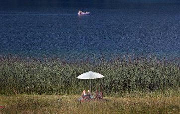 12 August 2020, Bavaria, Schwangau: People seek cooling under a parasol in a lido on the shores of the Alpsee. Photo: Karl-Josef Hildenbrand\/dpa
