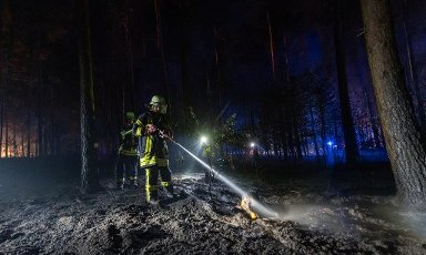 12 August 2020, Lower Saxony, Essel: Firefighters extinguish nests of embers in a piece of forest. Because of a large-area fire in the Heidekreis, the weekend area Esseler Wald was evacuated in the evening, according to police reports. Photo: Philipp Schulze\/dpa