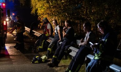 12 August 2020, Lower Saxony, Essel: Firefighters pause at the edge of the highway. Because of a large scale fire in the Heidekreis, the weekend area Esseler Wald was evacuated in the evening, according to police reports. Photo: Philipp Schulze\/dpa