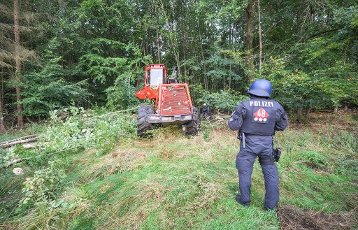 01 October 2020, Hessen, Stadtallendorf: A policeman is standing at a harvester in the Herrenwald during the beginning clearing works. Activists currently want to prevent the clearing of the Herrenwald. The activists are demonstrating against the planned expansion of the A49 and for the preservation of the Herrenwald and Dannenröder forests, which would fall victim to the planned expansion. Photo: Andreas Arnold\/dpa