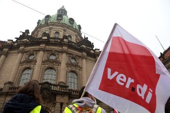 01 October 2020, Brandenburg, Potsdam: Demonstrators have gathered in front of the city hall in the morning and wave a Verdi flag. In connection with the round of collective bargaining for the public service, the United Services Union (Verdi) has called on the employees, apprentices and trainees at the state capital Potsdam to go on a first, all-day warning strike. Photo: Soeren Stache\/dpa-Zentralbild\/ZB