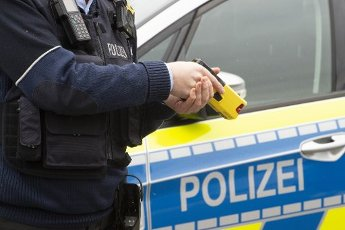Policeman with a distance electro pulse device (DEIG) in his hand, stands in front of a patrol car, feature, symbol photo, border motif, NRW Interior Minister Herbert Reul starts piloting the distance electro pulse devices (DEIG) at the police in North Rhine-Westphalia, in the police headquarters in Dorrtmund, January 15, 2021, Â | usage worldwide