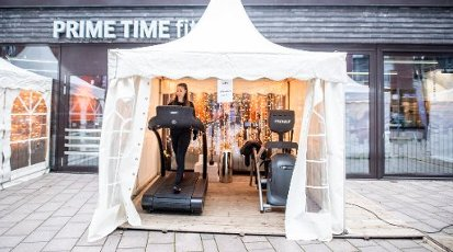 """dpatop - 15 January 2021, Hamburg: Elena trains on a treadmill in a tent in front of the """"Prime Time Fitness"""" gym in Hafencity. In order to be able to offer members a training session despite the lockdown, the company has moved some fitness equipment into tents outside. Here, two pieces of training equipment are available for customers at a time, with the notice """"1 household per tent"""". Photo: Daniel Reinhardt\/dpa"""
