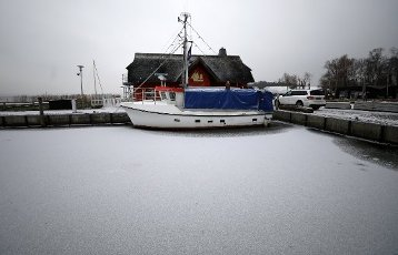 18 January 2021, Mecklenburg-Western Pomerania, Dierhagen: A fishing cutter lies in the ice in the Bodden harbour of the Baltic resort. Sub-zero temperatures and a thin blanket of snow over the landscape create a wintry atmosphere in the north. Photo: Bernd Wüstneck\/dpa-Zentralbild\/dpa