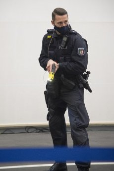 Police officer with a distance electronic pulse device (DEIG) in his hand, feature, symbol photo, border motif, NRW Interior Minister Herbert Reul starts piloting the distance electronic pulse devices (DEIG) at the police in North Rhine-Westphalia, in the Dorrtmund police headquarters, January 15, 2021, Â | usage worldwide