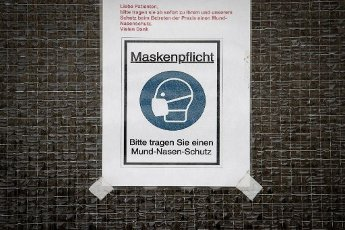 03 March 2021, Lower Saxony, Osnabrück: The obligation to wear a mask is indicated on the entrance door of a doctor\'s surgery. Photo: Friso Gentsch\/dpa
