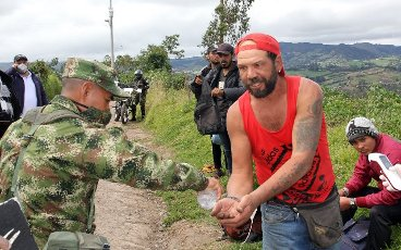 A Colombian soldier delivering disinfectant to foreign citizens who passed from Ecuador to Colombia, in Ipiales, Colombia, 04 April 2020 (Issued 05 April 2020). Colombia
