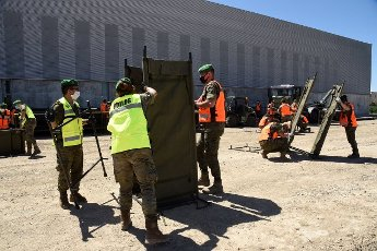 Several Spanish troops set up a tent outside a sport pavilion to shelter 28 temporary pickers, who tested positive for COVID-19, in the village of Albalate de Cinca, bordering with Lleida, in Aragon, northeastern Spain, 16 July 2020. The workers are confined in the pavilion to avoid the spreading of coronavirus. EFE\/ Javier Blasco