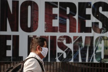 """MEXICO CITY, MEXICO -APRIL 10: A man walks wearing face mask front a poster that says """"You are not the same""""during the lockdown as measure to contain the spread of the SARS-CoV-2 which causes the COVID-19 disease.have confirmed in the country 20 new deaths in 24 hours due Coronavirus On April 10, 2020 in Mexico City, Mexico"""