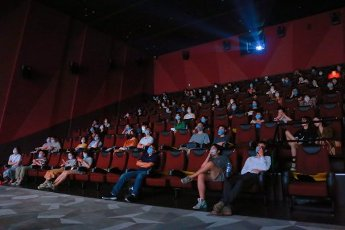The audience, mostly seated in pairs, watch a film in a cinema in Shanghai, China Friday, Aug. 14, 2020. The authority has lifted the cap on the theatres to 50% of the seats as the coronavirus pandemic eases in China
