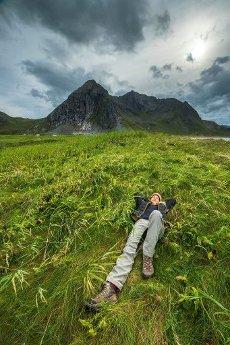 Woman lies pleasurably in a meadow in front of threatening mountain range, Skagsanden, Flakstad, Lofoten, Nordland, Norway