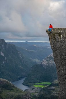 Single person sitting on the edge at the rock plateau, Preikestolen rock pulpit, Lysefjord, Ryfylke, Rogaland, Norway