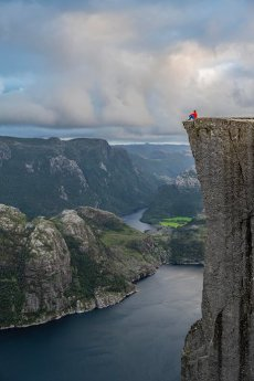 Single person sitting on rock plateau, Preikestolen rock spire, Lysefjord, Ryfylke, Rogaland, Norway