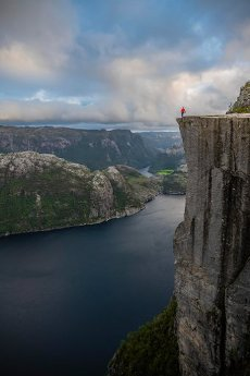 Single person on rock plateau, Preikestolen rock spire, Lysefjord, Ryfylke, Rogaland, Norway