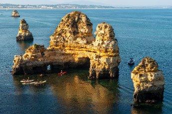 Kayakers paddling around rock formations in the sea, Ponta da Piedade, rugged sandstone coastline, Algarve, Lagos, Portugal