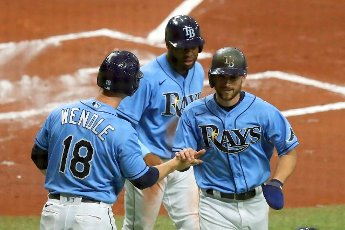 ST. PETERSBURG, FL - MAY 13: Joey Wendle (18) of the Rays welcomes home Brandon Lowe (8) and Manuel Margot (13) in background during the regular season game between the New York Yankees and the Tampa Bay Rays on May 13, 2021 at Tropicana Field in St. Petersburg, FL. (Photo by Cliff Welch\/Icon Sportswire