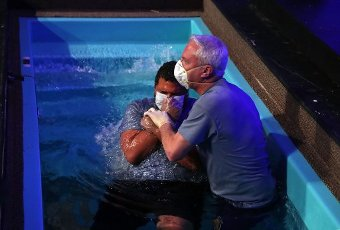 Senior pastor Scott Nichols baptizes Jerry Phiri at Crossroads Community Church in Carol Stream on April 9, 2020. (Chris Sweda/Chicago Tribune/TNS)