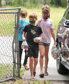 From left, Aiden Langton, 10, Luc Dagenais, 10, and Jocelyn Dagenais, 11, help deliver meals provided by Orange County Public Schools to needy families in Bithlo, Fla., Friday, April 10, 2020. The volunteer delivery effort was organized by a group of east Orlando PTA moms in response to the coronavirus crisis. (Joe Burbank/Orlando Sentinel/TNS)