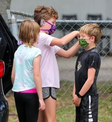 Jocelyn Dagenais, 11, adjust the mask of her younger brother, Luc Dagenais, 10, as McKenzie Langton, 9, left, looks on as the students help deliver meals provided by Orange County Public Schools to needy families in Bithlo, Fla., Friday, April 10, 2020. The volunteer delivery effort was organized by a group of east Orlando PTA moms in response to the coronavirus crisis. (Joe Burbank/Orlando Sentinel/TNS)