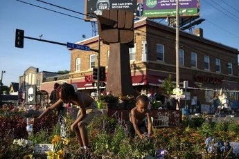 Two children water the plants at the memorial in the 38th Street and Chicago Avenue intersection near where George Floyd was killed in Minneapolis Police custody in late May. (Aaron Lavinsky\/Minneapolis Star Tribune\/TNS