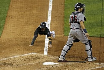 Atlanta Braves catcher Travis d\'Arnaud (16) stands by as the Miami Marlins\' Eddy Alvarez dives in to score on a sacrifice bunt by teammate Magneuris Sierra during the fourth inning at Marlins Park in Miami on Friday, Aug. 14, 2020. (David Santiago\/Miami Herald\/TNS